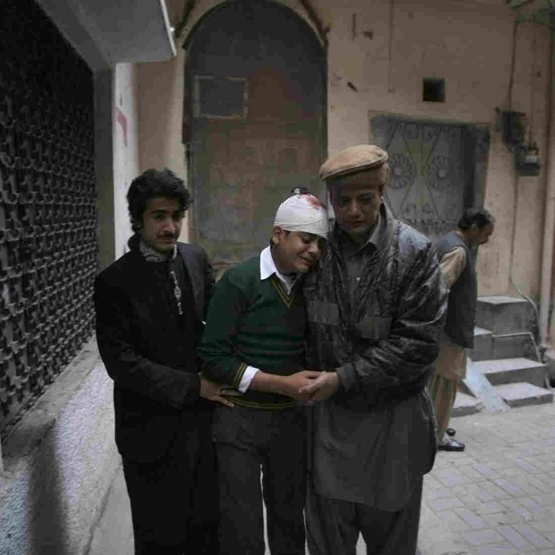 The uncle and cousin of injured student Mohammad Baqair (center) comfort him as he mourns the death of his mother, who was a teacher at the school that was attacked.