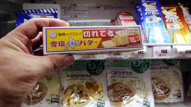 A customer picks up a block of butter at a food store in Tokyo on Nov. 10th. Japanese shoppers are up in arms over a serious butter shortage that has forced Tokyo to resort to emergency imports, as some grocers limit sales to one block per customer.