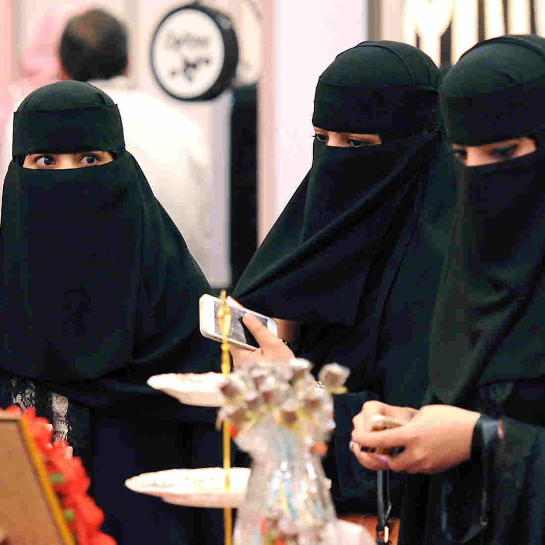 Saudi Arabian women wear their traditional face covering, the niqab, at a coffee and chocolate exhibition in the capital Riyadh on Monday. A prominent religious figure said on Twitter that the face veil is not mandatory, sparking a heated national debate.