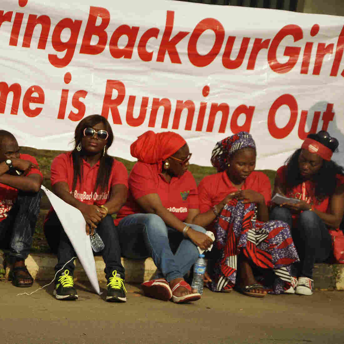 """Members of the Abuja """"Bring Back Our Girls"""" protest group sit during a march in continuation of the Global October movement. Once again, Boko Haram militants are implicated in killings and mass kidnapping in northeastern Nigeria."""
