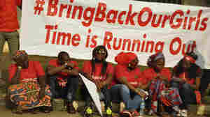 "Members of the Abuja ""Bring Back Our Girls"" protest group sit during a march in continuation of the Global October movement. Once again, Boko Haram militants are implicated in killings and mass kidnapping in northeastern Nigeria."