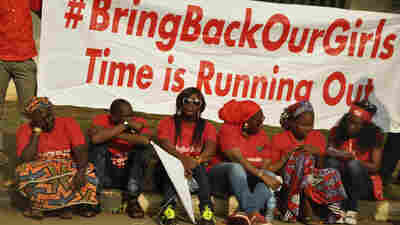 "Members of the Abuja ""Bring Back Our Girls"" protest group sit during a protest march, in continuation of the Global October. Once again, Boko Haram militants are implicated in killings and mass kidnapping in northeastern Nigeria."