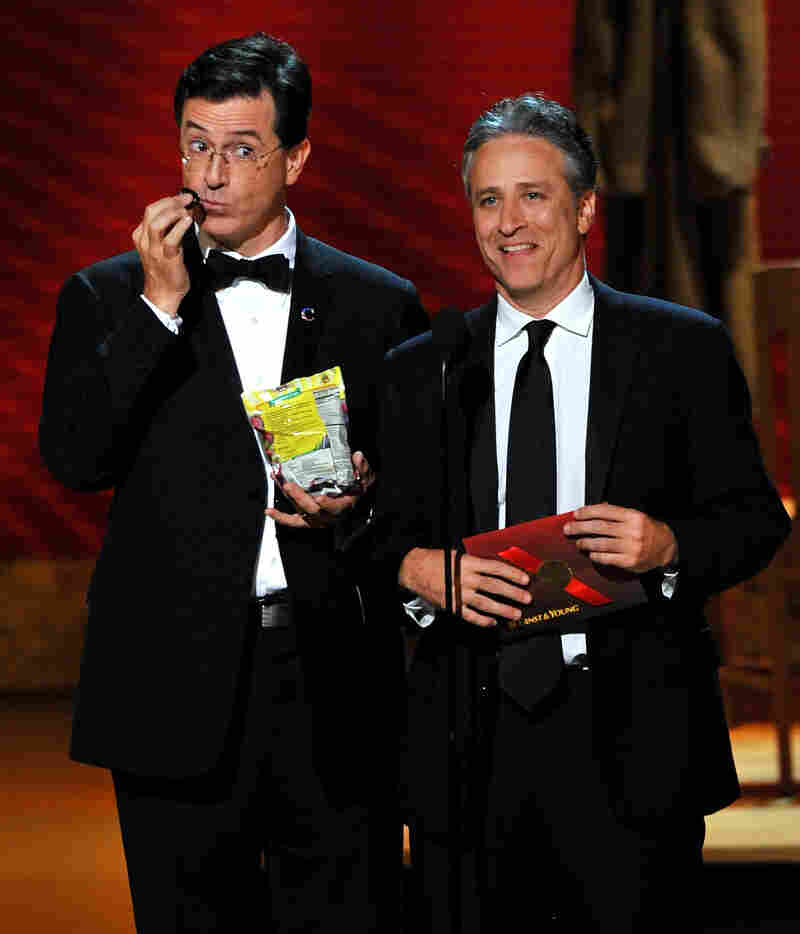 In 2008, Stephen Colbert (left) and Jon Stewart present during the Emmy Awards. Colbert got his start satirizing the news as a correspondent on The Daily Show two years before Stewart took it over.