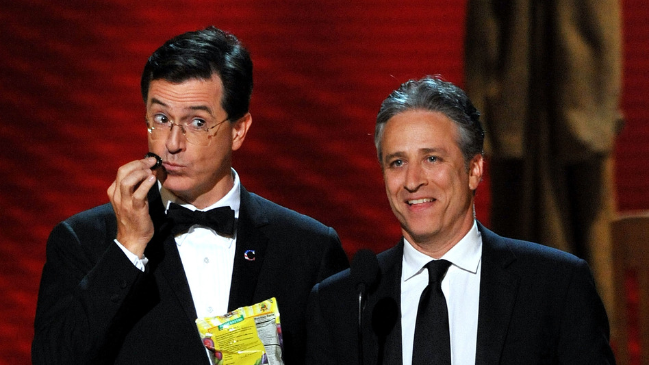 In 2008, Stephen Colbert (left) and Jon Stewart present during the Emmy Awards. Colbert got his start satirizing the news as a correspondent on <em>The Daily Show </em>two years before Stewart took it over.