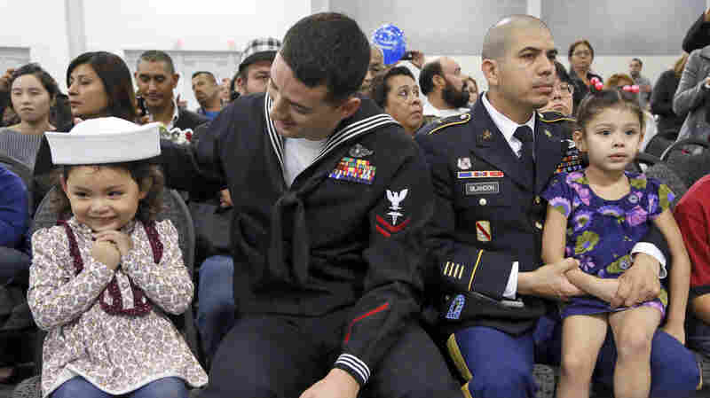 Navy Petty Officer Jimmy Dial (left) sits with his daughter, Kimberly, beside U.S. Army soldier Henri Blandon and his daughter as the men's wives and the girls' mothers become U.S. citizens at a naturalization ceremony last month in Ontario, Calif.