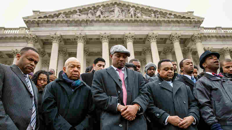 Congressional staff members gather at the Capitol to raise awareness of the recent killings of black men by police officers, both of which did not result in grand jury indictments, on Dec. 11. They are joined by Rep. Elijah Cummings, D-Md. (second from left), and Senate Chaplain Barry Black (far right).
