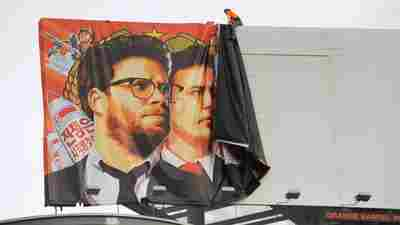 Workers remove a banner for The Interview from a billboard in Hollywood, Calif., on Thursday, a day after Sony announced was cancelling the movie's Christmas release.