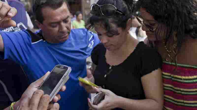 Cubans try to connect to the Etecsa server during a May 9 service outage as they wait with other customers outside the offices of the state telecom monopoly in Havana, Cuba. Cuba's government has blamed technological problems on a U.S. embargo. Critics of the government have said it deliberately strangles the Internet to mute dissent. Normalization of U.S.-Cuba relations may prove who's right.