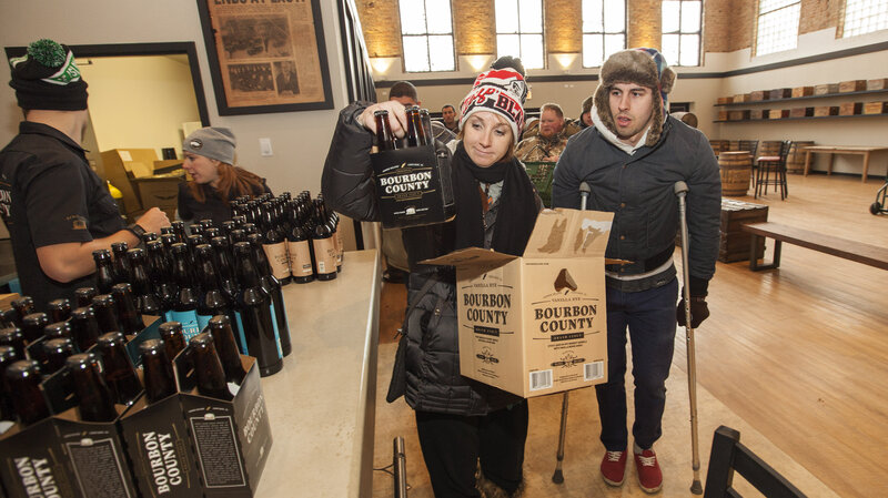 A craft beer fan picks up a six-pack of Goose Island Beer Co.'s limited Black Friday release of Bourbon County Brand Stout on Nov. 26 in Chicago.
