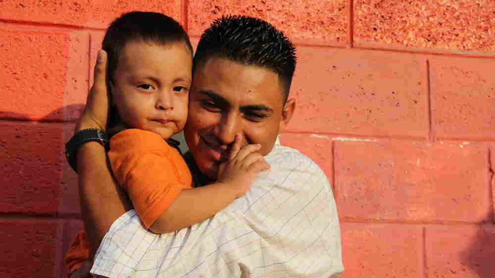 Jose Hernandez greets his young son outside El Edén, the center where deported kids are sent in Honduras. His wife and two young children had just been deported from Mexico.