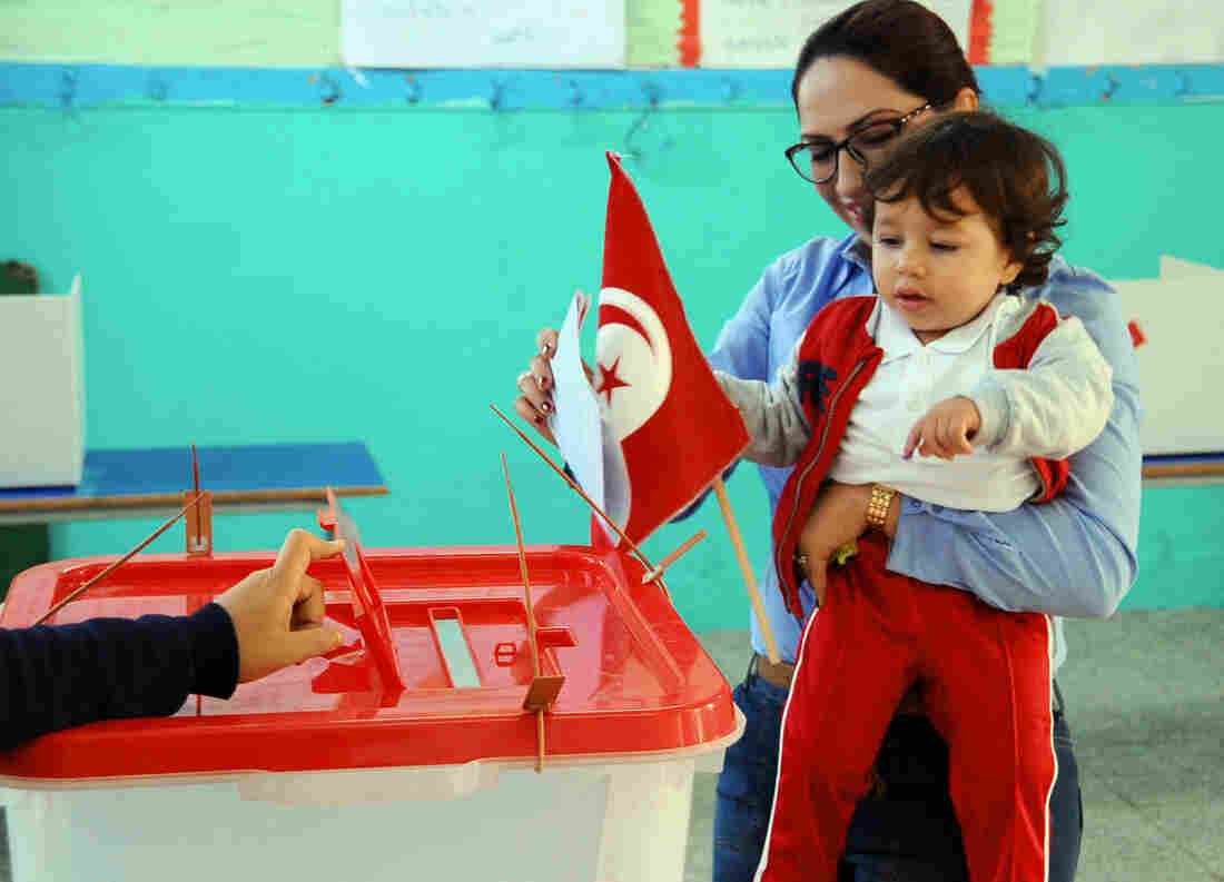 A woman votes in the first round of the Tunisian presidential election on Nov. 23. The election went smoothly, but no candidate won 50 percent of a vote, forcing a runoff between the top two on Sunday.