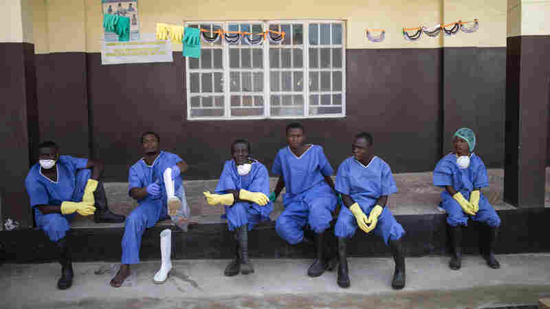 Health workers rest outside a quarantine zone at a Red Cross facility in the town of Koidu, Kono district in Eastern Sierra Leone on Friday. The World Health Organization says the number of Ebola deaths in the current outbreak has exceeded 7,000.