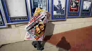 "A worker carries a poster for the movie The Interview away from its display case at a theater in Atlanta. ""It feels like the margin's narrowed about what kind of movies Hollywood will be making,"" says veteran Hollywood producer Stephanie Striegel."