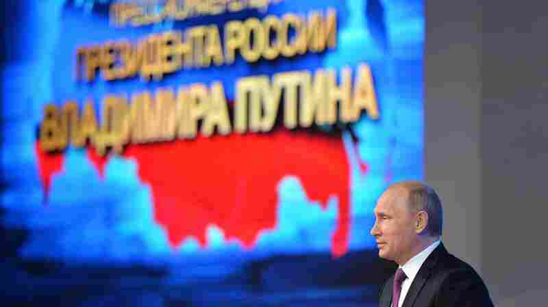Russian President Vladimir Putin speaks in front of the map of the Russian Federation, with Crimea on the left of the map, during his annual news conference in Moscow, Russia, on Thursday. The Kremlin has responded angrily to the latest round of U.S.-EU sanctions over the annexation of Crimea.