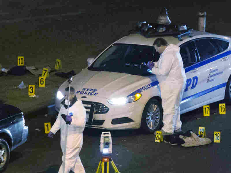 Investigators work at the scene where two NYPD officers were shot on Saturday.