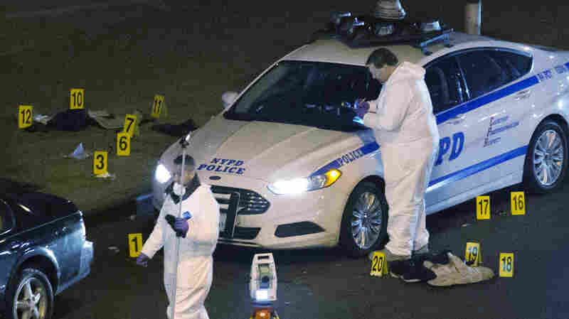 Investigators work at the scene where two NYPD officers were shot, on Saturday.