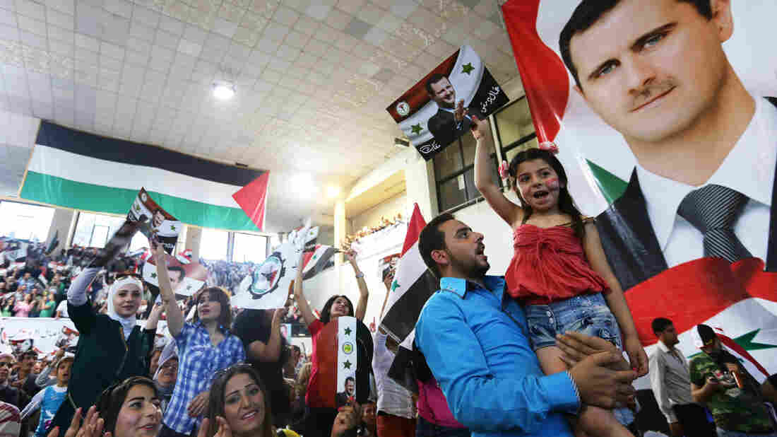 Syrians in the capital Damascus hold posters with portraits of President Bashar Assad ahead of the country's June election. He was overwhelmingly elected in a vote that Western countries called illegitimate.