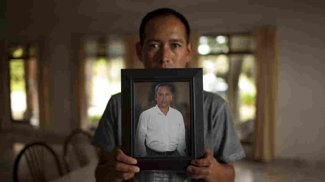 Pablo Cote holds a photo of his deceased father of the same name in July 2013 in Tlaxcala, Mexico. Cote was kidnapped while driving back from the U.S. border to the east-central state of Tlaxcala. He was beaten to death, part of the mass killing of 193 bus passengers and other travelers by the Zetas.