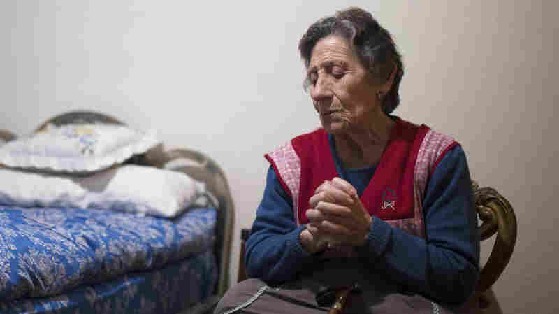 Carmen Martinez Ayuso, 85, prays during her eviction from her home in Madrid, Spain, on Nov. 21. A professional Spanish soccer team, Rayo Vallecano, has come to her aid, promising to pay her housing costs for the rest of her life.