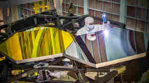 Larkin Carey, an optical engineer with Ball Aerospace, examines two test mirror segments designed for the James Webb Space Telescope. The mirror for the scope is extremely powerful, but heavy and pricey.