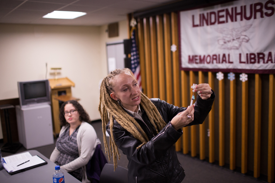 Tina Wolf demonstrates the use of naloxone to community members in Lindenhurst, N.Y., during an overdose prevention training. Georgia Dolan-Reilly (left) of the Suffolk County Prevention Resource Center helped with the training. (Kevin Hagen for NPR)