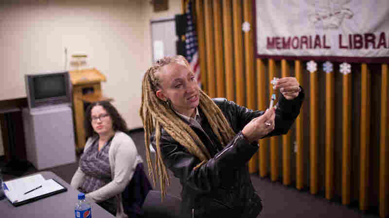 Tina Wolf demonstrates the use of a syringe to community members in Lindenhurst, N.Y., during an overdose prevention training. Georgia Dolan-Reilly (left), of the Suffolk County Prevention Resource Center helped with course.