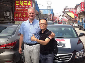 """NPR reporter Frank Langfitt and one of his """"customers,"""" a biotech worker, whom he drove to a self-help conference in Shanghai's sprawling Pudong District."""