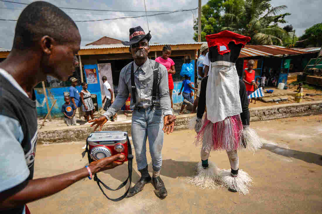Liberian Santa (right) sings and dances in downtown Monrovia. Passers-by toss him coins so he'll have a happy and prosperous new year.