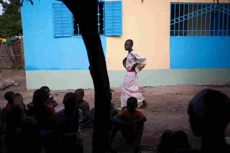 A girl walks past a coed class at the Quranic school at the home of Imam Ibrahima Diallo. Students come in the afternoon, after their regular school session ends, to memorize passages of the Quran.