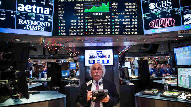 A New York Stock Exchange trader works on the floor on Dec. 17. Stocks rose nearly 300 points after the Federal Reserve announced it plans to begin raising interest rates next year.