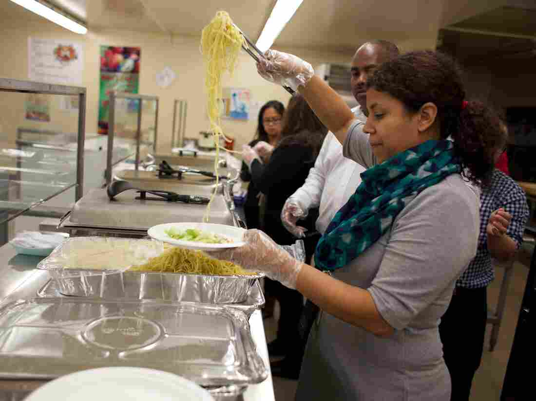 Amaya Weiss, who runs the food pantry at the John Still K-8 School in Sacramento, serves up a spaghetti dinner at the school's monthly family night.