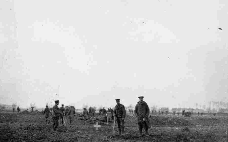 """The 1914 Christmas truce was an opportunity for both sides to bury their dead. Alan Wakefield of the Imperial War Museum, describes the photo: """"Four British soldiers in the foreground (are) beside a grave, a recently dug grave. And a mixed group of German and British in the background, actually digging fresh graves for other casualties."""""""