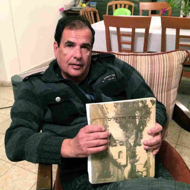 Itzhak Levy, seated in his Jerusalem apartment, holds a copy of a book on his family's history. Levy's ancestors were expelled from Spain. But he says he's not interested in the offer of Spanish citizenship because he doesn't feel that Europe today is supportive of Israel.