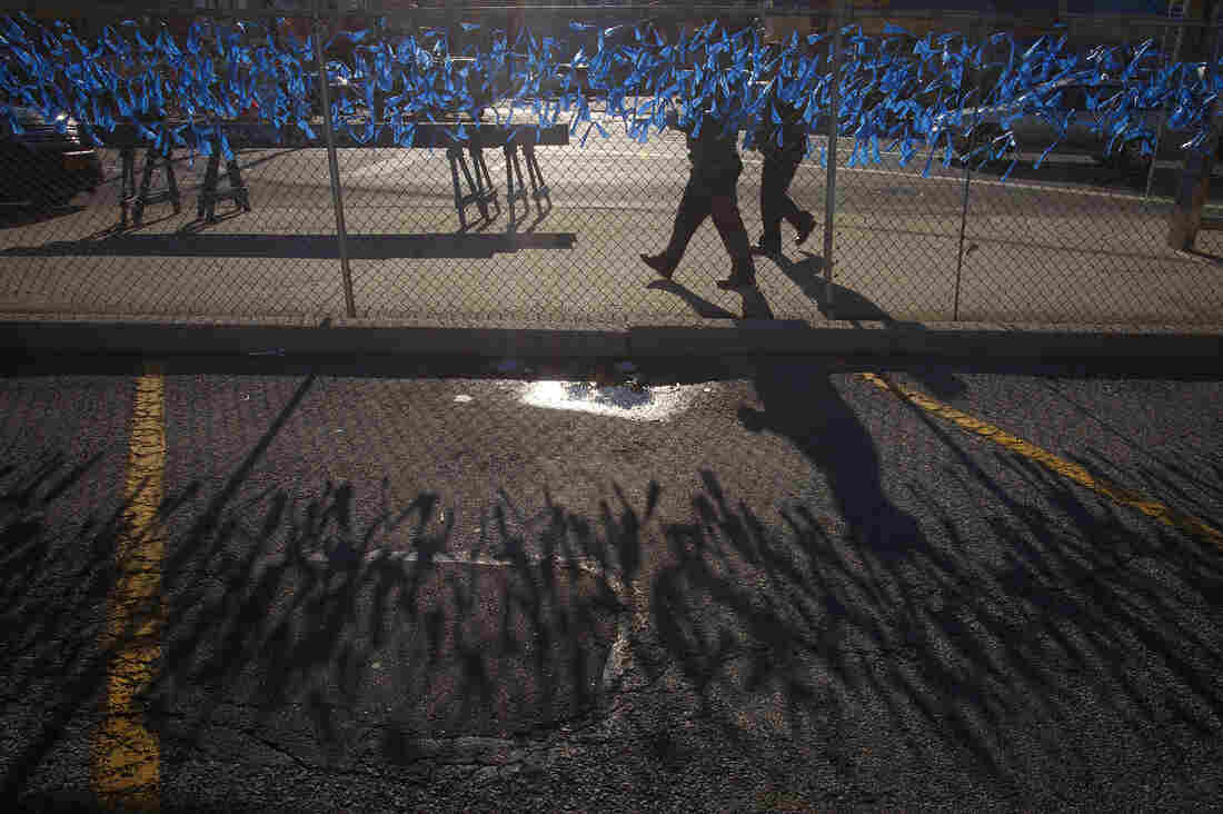 Police officers walk past a fence covered in blue ribbons as a makeshift tribute near Christ Tabernacle Church.