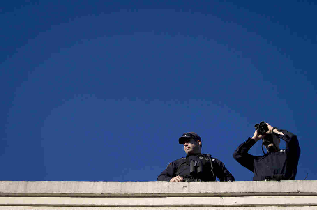 Police snipers stand on a roof as they monitor the area for Ramos' wake.