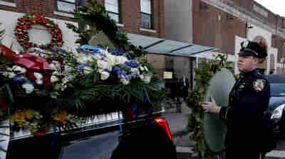 A New York Police Department officer loads flowers onto a vehicle outside of Officer Rafael Ramos' funeral at Christ Tabernacle Church, in the Glendale section of Queens, on Saturday.