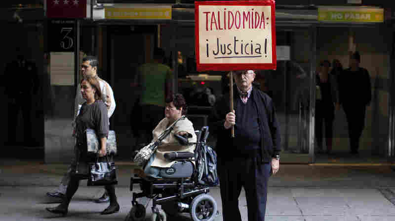 """A Thalidomide victim leaves a Spanish court in a wheelchair while a protestor holds a sign reading """"Thalidomide, Justice!"""" during a trial in Madrid in October 2013. Thousands of babies across Europe were born with abnormalities including missing limbs when expectant mothers were prescribed thalidomide in the 1950s and later."""