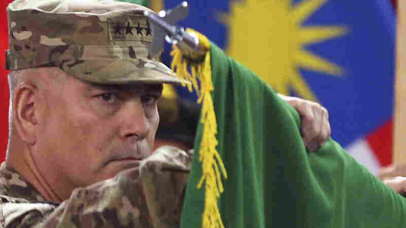 "Commander of the International Security Assistance Force (ISAF), Gen. John Campbell opens the ""Resolute Support"" flag during a ceremony at the ISAF headquarters in Kabul on  Sunday."