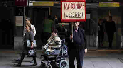 """A Thalidomide victim leaves a Spanish court in a wheelchair while a protestor holds a sign reading """"Thali"""