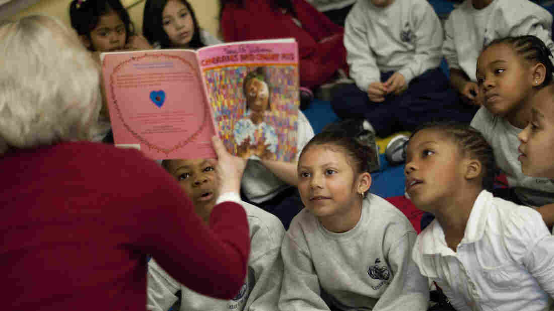 First Book President and CEO Kyle Zimmer reads to children during a book distribution event.
