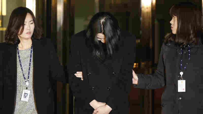 Cho Hyun-ah (center) leaves for a detention facility today following a court order. Cho served as head of in-flight service for Korean Airlines until earlier this month. Her conduct aboard an aircraft over a packet of improperly served macadamia nuts led to her resignation. She is accused of violating South Korea's aviation safety laws.
