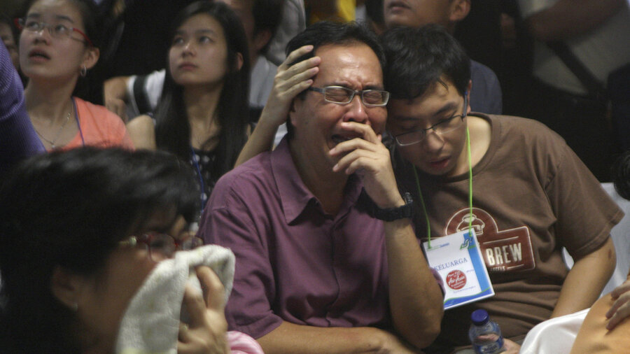 Relatives of passengers of the missing AirAsia Flight 8501 react upon seeing the news on television about the findings of bodies on the waters near the site where the jetliner disappeared in Surabaya, East Java, Indonesia, on Tuesday.