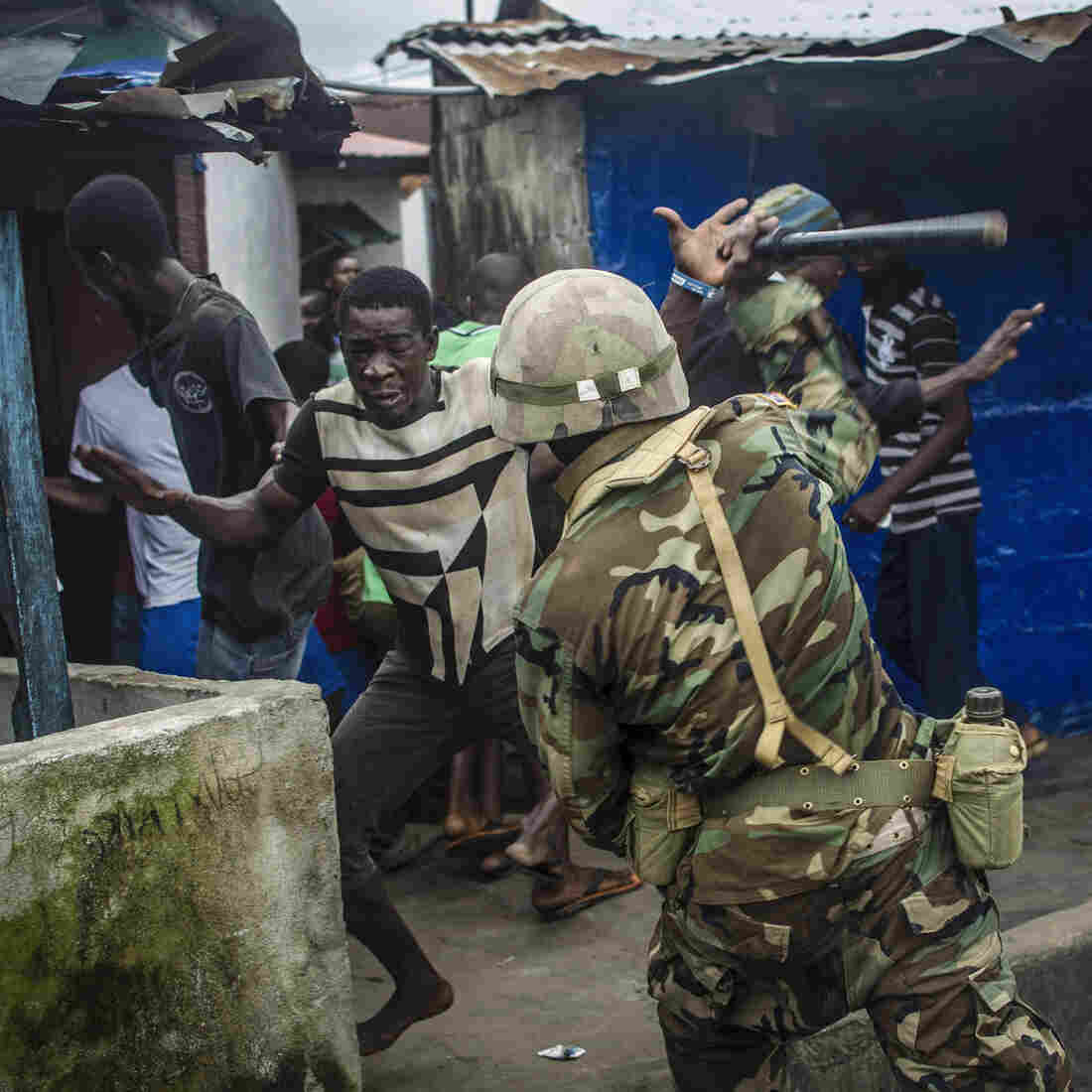A soldier hits a protestor with a baton during unrest in West Point after the area was quarantined in a bid to prevent the spread of Ebola.