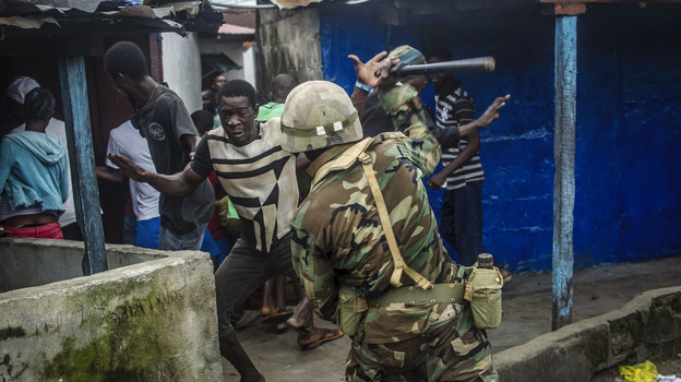 A soldier hits a protestor with a baton during unrest in West Point after the area was quarantined in a bid to prevent the spread of Ebola. (Tommy Trenchard for NPR)