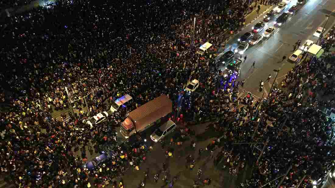 Emergency vehicles navigate the New Year's Eve crowd in Shanghai after a stampede by revelers in the historic riverfront district. At least 35 people were killed.