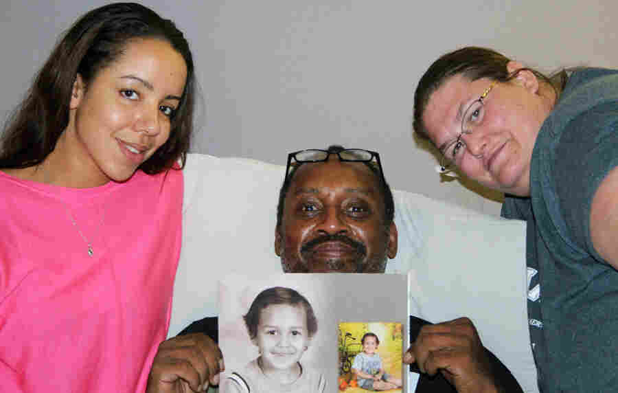 Megiddëh Goldston (left) with Heidi Hameed (right) and her husband, Raphael, at StoryCorps in Colorado Springs, Colo. Raphael holds photos of his son, Ish — short for Ishaq — who was killed in July when he was struck by a car driven by Megiddëh's sister.