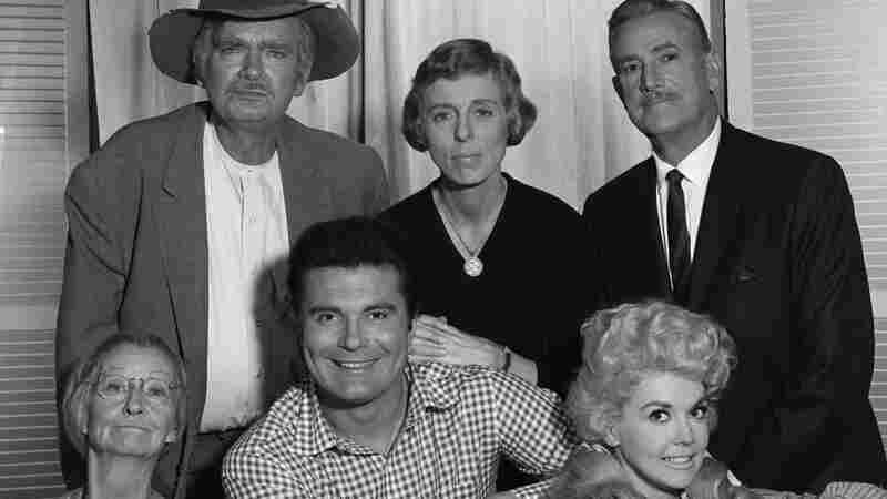 "Donna Douglas as Elly May Clampett, lower right. Clockwise from upper left are Buddy Ebsen (as Jed Clampett), Nancy Kulp (as Jane Hathaway), Raymond Bailey (as Milburn Drysdale), Douglas, Max Baer Jr. (as Jethro Bodine) and Irene Ryan (as ""Granny"")."