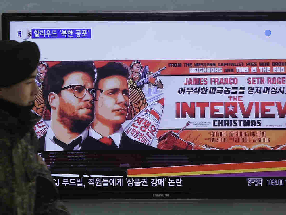 A South Korean army soldier walks near a TV screen showing an advertisement of Sony Picture's The Interview, which sparked condemnation in North Korea, which allegedly hacked the studio.
