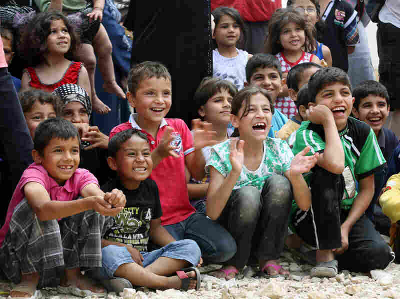 Syrian refugee children smile while watching members of Clowns Without Borders perform in June at a Syrian refugee camp in Lebanon. Various chapters of the group did several tours through camps on the Syrian border in 2014.