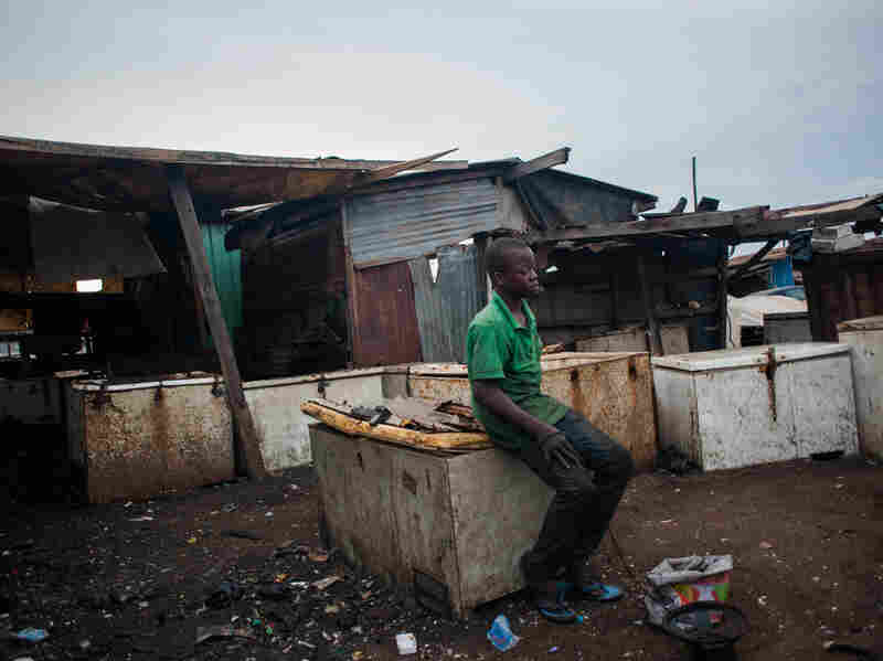 Kwesi Bido rests on an old chest freezer at Agbogbloshie. The dump is full of hazards for the boys and men who pick through it.